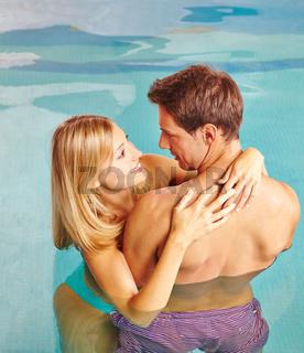 Paar umarmt sich im Wasser im Schwimmbad