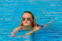Young woman swimming in outdoor pool