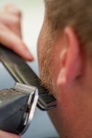Hairdresser Shaving Man's beard With Hair Trimmer or hair clipper, seen from behind the customer.