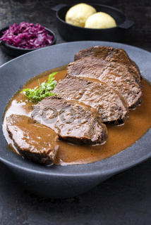 Traditional braised marinated German Sauerbraten from beef with blue kraut in spicy brown sauce as closeup in a modern design cast iron plate