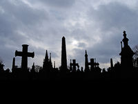 old gothic style gravestone in silhouette with tall memorials and crosses against an overcast cloudy sky