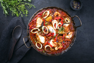 Traditional Brazilian fish stew moqueca capixaba with fish filet and squid rings in tomato sauce as top view in a rustic pan