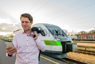 Young handsome businessman using mobile phone in front of train at railway station