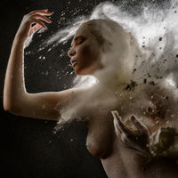Girl topless in a cloud of white dust studio portrait