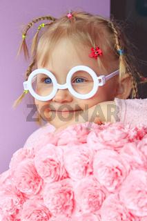 Little girl in plastic glasses smile near paper flowers made from papier-mache.