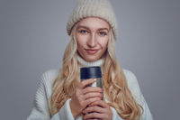 Pretty woman cradling a hot beverage in winter