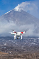 Flying drone quadcopter UAV aerial photography in sky on background of volcano eruption