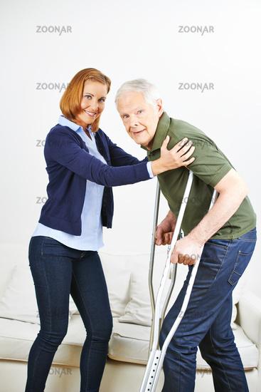 Senior mit Krücken bei der Reha