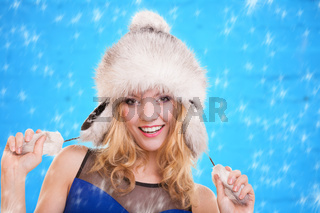 Fashion woman happy smiling girl in warm clothing fur hat on blue winter snow flakes background