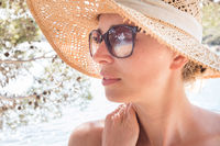 Close up portrait of no makeup natural beautiful woman wearing straw sun hat and sun glasses on the beach in shade of a pine tree