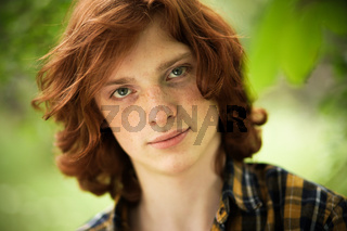 Red-haired freckled man posing in sunny day outdoors. Young foxy green-eyed handsome stands on green floral blurred background. Male beauty concept. Toned image
