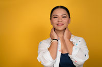 Skin care concept. Pretty woman smiles touching her neck with hands. Copy space at left side. Happy mid aged Asian woman posing in studio on yellow background