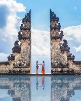 Tourists take photos at the gates of Pura Lempuyang Luhur Temple in Bali, Indonesia