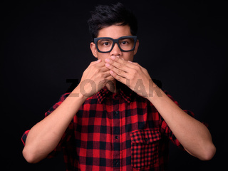Portrait of young Asian hipster man against black background