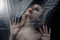 Young beauty sad woman trapped behind a plastic sheet as protection against COVID-19.