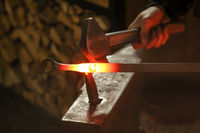 A blacksmith uses a hammer to work a glowing piece of metal on the anvil
