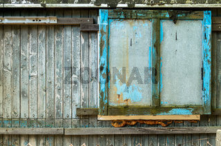 Old grungy closed Window Shutter Wall of Cabin.