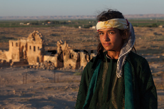Young middle eastern girl standing in front of the ruins of ancient Harran University in Sanliurfa,