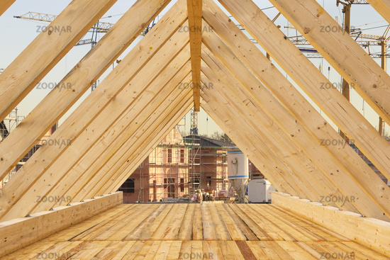 Construction site with roof beams at top of a newly built house