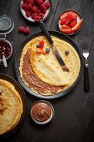 Delicious chocolate homemade pancakes on black ceramic plate