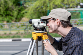 Surveyor engineer worker making measuring with geodetic optical level