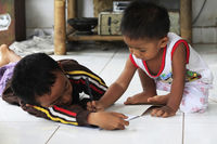 Children of an Indonesian artist paint while sitting on the floor. Bali is famous for talented artis