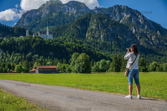 Female tourist taking photos Neuschwanstein Castle Bavarian Alps Germany