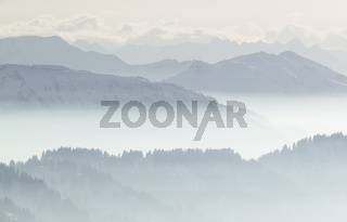 Snow Mountains in low lying inversion valley fog. Silhouettes of foggy Mountains and trees. Scenic snowy winter landscape. View from Stuiben Swiss Alps, Allgau, Bavaria, Germany.