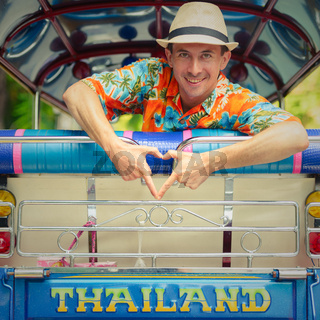 Happy young handsome tourist man riding the tuk tuk in Bangkok city