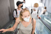 Portrait of casual yound woman uses escalators in the department store wearing protective mask as protection against covid-19 virus. Incidental people on the background