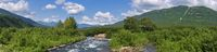Panorama view of beautiful summer landscape - stream water of mountain river and green forest on sunny day with white clouds in blue sky
