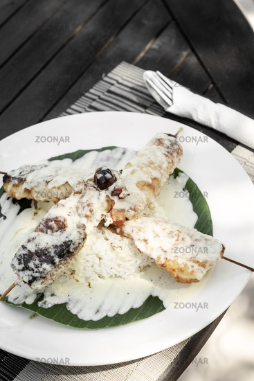 fish skewers with creamy coconut sauce and rice in vietnam