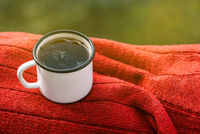 White mug with tea on a red sweater. Metal mug on the nature in the summer or spring. Morning breakfast. The concept of the approaching summer of romance and love. Cozy atmosphere.