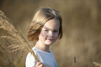 Beautiful little girl in a meadow with a bouquet of herbs.