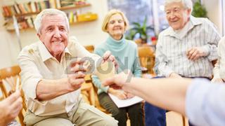 Psychotherapeutin spielt mit dementen Senioren in einer Gruppenpsychotherapie