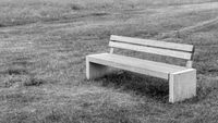 Gray bench stands alone in a meadow