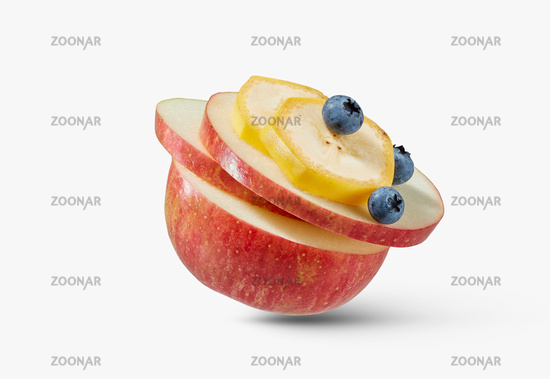 Fresh ripe natural apple with slices of banana and blueberries on a white background.