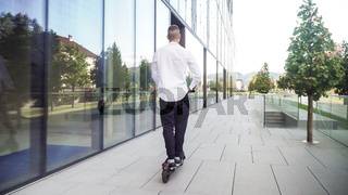 young casual business student man riding electric scooter