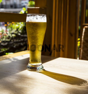 Beer in a glass glass on a wooden table in a summer