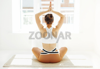 Back view of unrecognizable female in sportswear sitting with crossed legs