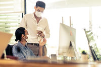 Businessmen wear face mask dicuss in new normal office