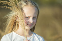 Beautiful little blonde girl with a bouquet of herbs.Child in a beautiful summer field.