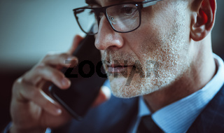 Handsome businessman talks on mobile phone. Close up portrait of Caucasian man with gray stubble answering the call. Business concept