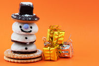 A candy snowman and a stack of present boxes isolated on orange background