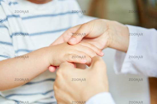 Osteopath macht Akupressur an der Hand von Kind