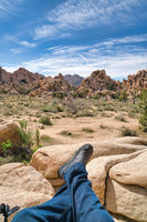 Man resting on rocks overlooking desert scenery at Joshua Tree National Park