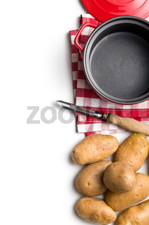 uncooked potatoes and old wooden peeler