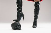 Crop woman in boots stepping on human skull
