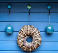 Porcelain objects and a wreath hang on a wall