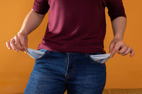 Empty pockets in blue jeans are shown by a young woman while facing the lens. Pulls pockets out. Lack of money.